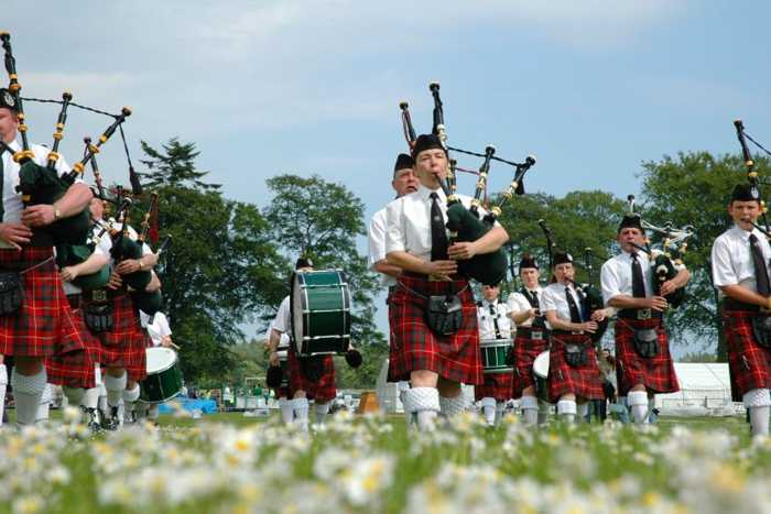 Marching Scottish band playing bagpipes in kilts